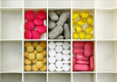 Various types of pills in a pill box Imagens