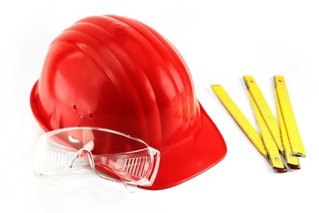 Red protection helmet and transparent protection glasses next to yellow meter Stock Photo