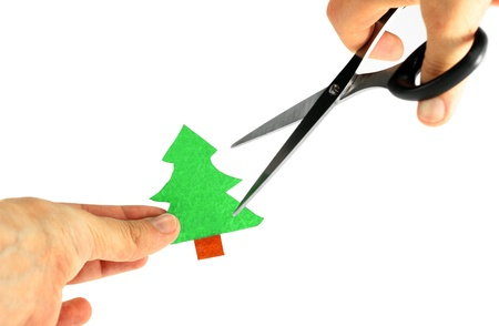 Small paper tree threatened by opened scissors