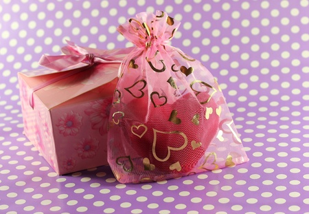 Present box and plus heart inside hearts decorated bag Imagens