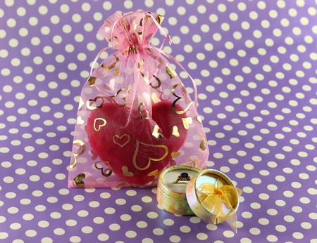 Ring in box next to hearts decorated bag with plush heart inside Imagens