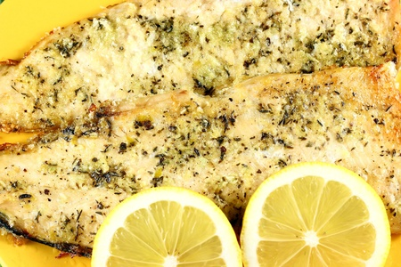 Cooked fish and lemons on yellow plate