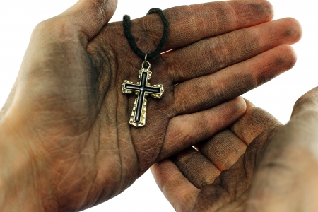 Dirty hands holding cross on white background photo