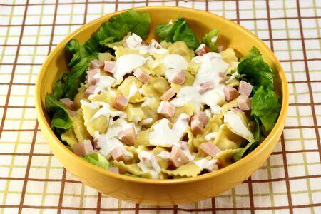 Pasta salad made from ravioli, ham, mayonnaise and lettuce
