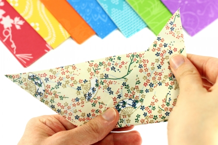 Hands folding origami, with origami paper in the background Stock Photo