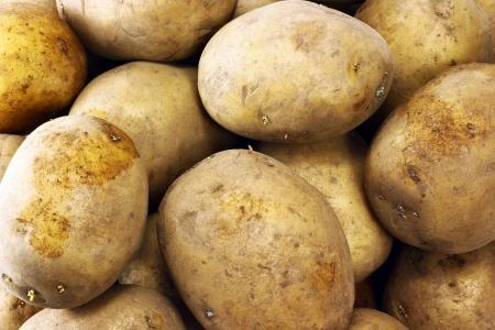 unpeeled: Dirty unpeeled potatoes pile