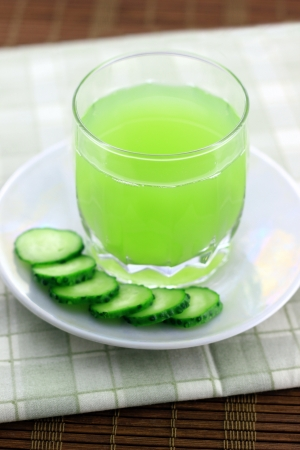 Cucumber juice next to cucumber slices