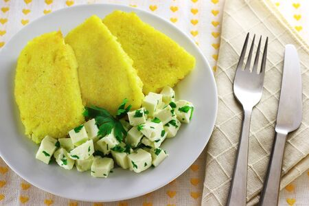Sliced polenta with cheese cubes