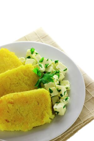 Sliced polenta with cheese cubes. Empty space for text.