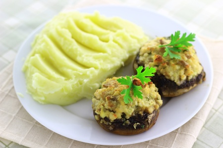 Champignon mushrooms stuffed with cheese, next to mashed potatoes Stock Photo