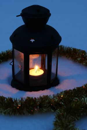 Candle lamp in snow surrounded by tinsel Stock Photo