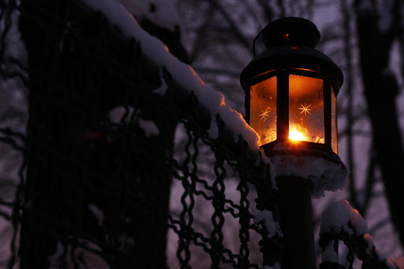 Candle lamp in winter at dusk