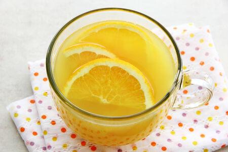 A cup of orange tea with orange slices inside