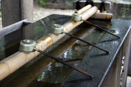 Purification basin at a shinto shrine. Ladles close up. Stock Photo