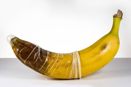 Condom over blackened banana. Concept for sexually transmitted infections, STD, STI