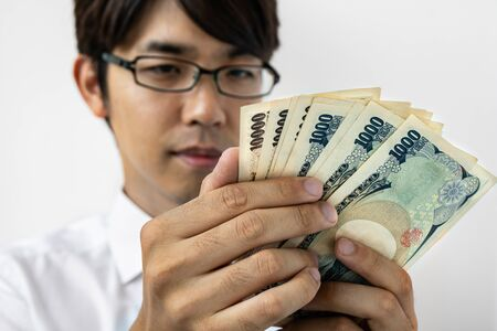 Young Japanese businessman counting money. Holding a stack of japanese yen banknotes. Isolated on white.