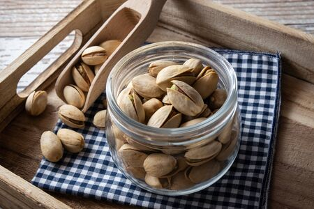 Pistachio nuts inside bowl on rustic table. Pistachios are healthy nuts packed with fiber and antioxidants. Natural source of vitamins, often found in vegetarian diets. Reklamní fotografie