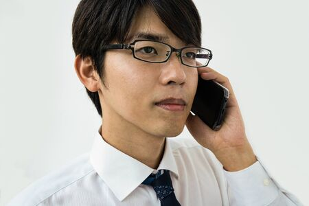 Young Japanese businessman talking on the phone. Isolated on white.