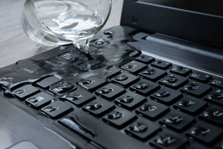 Water being spilled over laptop by accident. Keyboard is full of liquid and the computer is ruined.