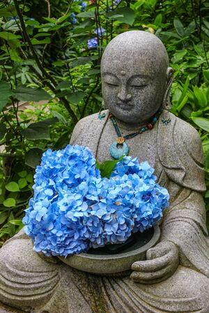 A buddha statue at a temple, holding fresh hydrangea flowers.