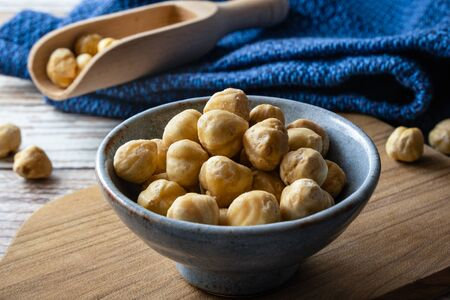 Macadamia nuts in modern bowl on table. Macadamia nuts are a source of protein packed with healthy vitamins.