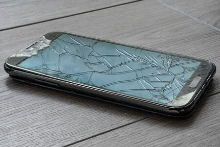 Broken smartphone on the floor. The screen is cracked and the phone is damaged.