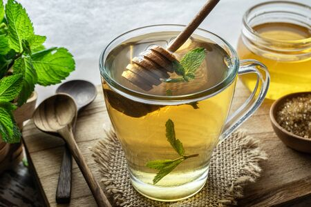 Honey being poured into a cup of mint tea. Mint tea is a healthy source of vitamins such as manganese and a natural medicine. Reklamní fotografie