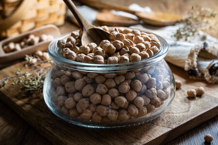 Dried uncooked chickpeas inside jar on table. Vegetarian food packed with minerals, iron, magnesium, potassium and other minerals. Healthy source of fiber. Reklamní fotografie