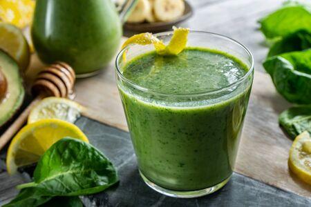 Green smoothie consisting of spinach, avocado, banana and lemon. Healthy vegetarian drink.