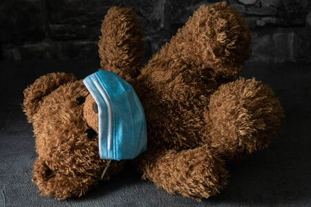 Teddy bear with surgical mask in dramatic light, concept of the novel coronavirus and its impact on children.Teddy bear with surgical mask in dramatic light, concept of the novel coronavirus and its impact on children.
