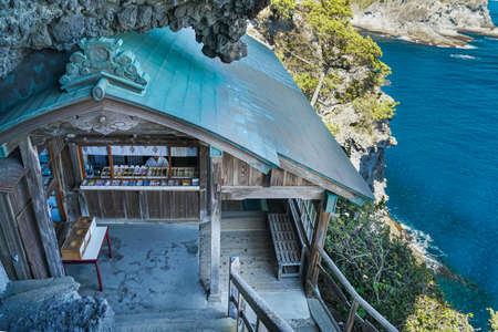 Japanese small shrine built inside a cliff by the ocean.