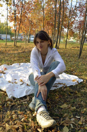 Young woman sitting on a blanket in autumn park photo