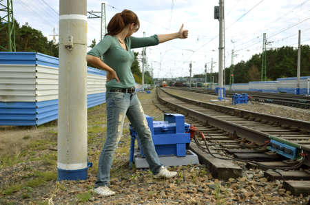 young woman hitchhiking along a rail photo