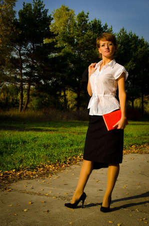 Business woman writing in a notebook in the autumn park on track Stock Photo - 15891632