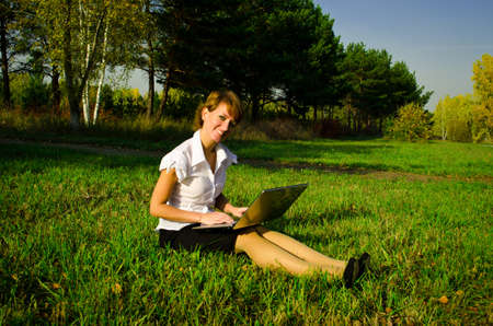 Businesswoman uses a laptop in autumn park sitting on the grass photo