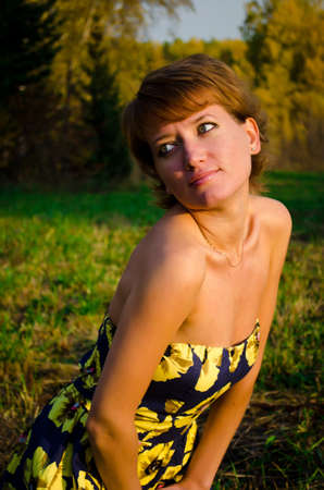 Young woman sitting on the grass in the autumn park photo