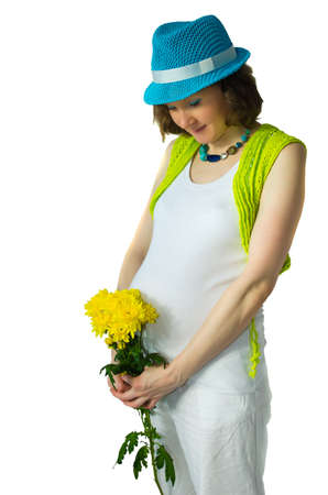 Adult pregnant woman in the studio with a yellow flower photo