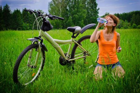 Young woman drinking water on grass photo