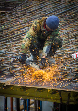 round rods: Construction worker cutting steel rods with electrical saw