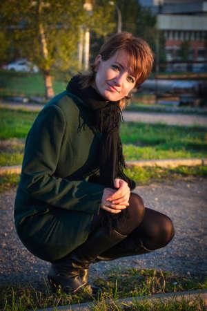 en cuclillas: Joven mujer en cuclillas en un abrigo de color verde oscuro en otoño parque en la puesta del sol Foto de archivo