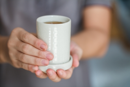 a woman is offering a cup of tea photo