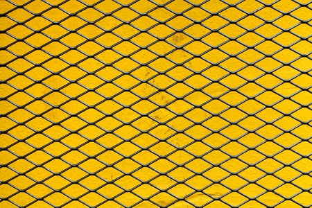 enclose: a iron net on a yellow wall Stock Photo