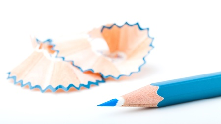 tip point of blue pencils and shavings from sharpening on white background