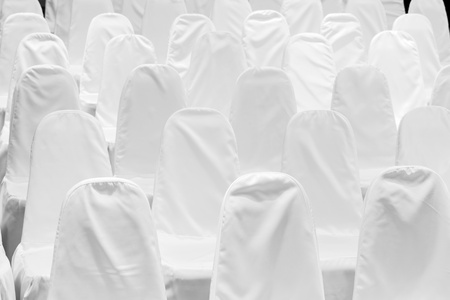 a lo of chairs with white covers photo