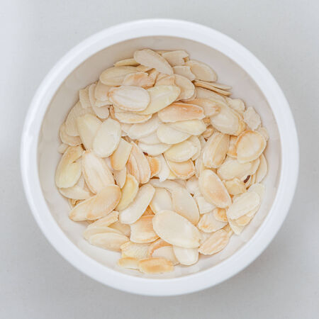 admixture: close up of sliced almond in white bowl