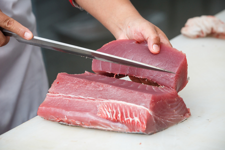 fish market: cutting tuna on a white table Stock Photo