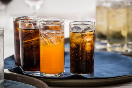 cold drink: many soft drink are on a tray