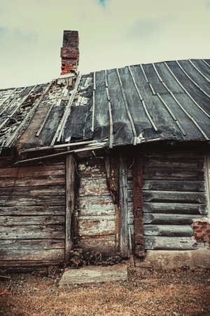 damaged roof: Old abandoned wooden barn at village outskirts