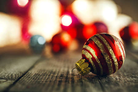 Red Christmas Bauble with an orament on rustic wooden board. Soft bokeh lights in the background. This can be used as Christmas or New Year's greeting card. Фото со стока