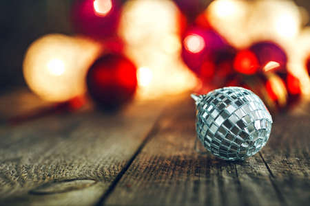 Mirrored pattern disco style Christmas Bauble on rustic wooden board. Soft bokeh lights in the background. This can be used as Christmas or New Years greeting card. Stock Photo